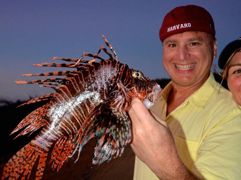 Roger J. Muller holding 2 lionfish
