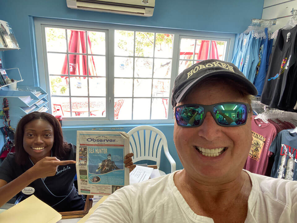Roger showing article in Jamaican newspaper.