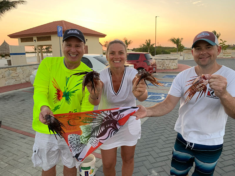 Lionfish hunters Roger J. Muller, Jr. and Jared Casperson hold up their catch with Roger's wife, Andrea Muller