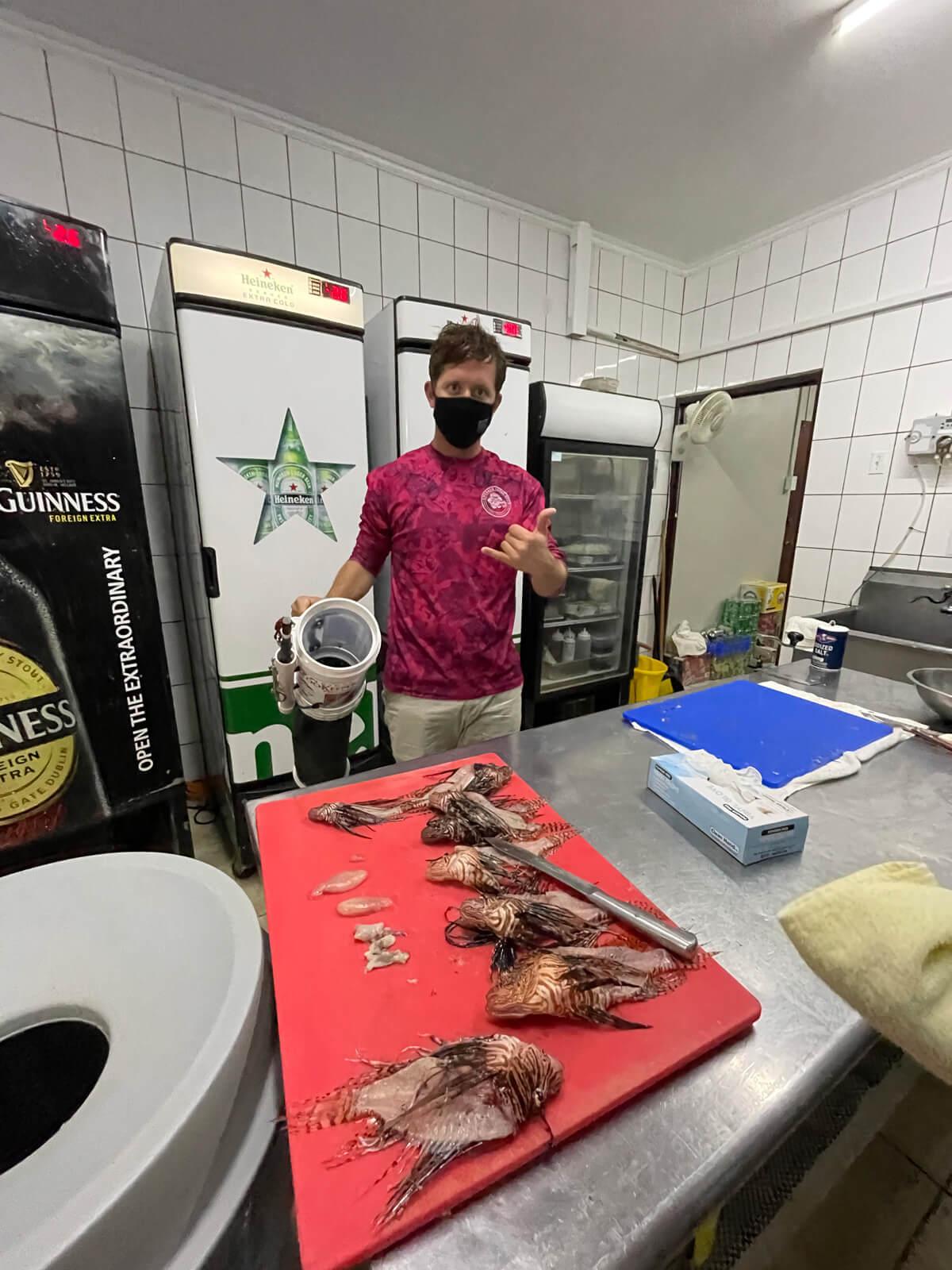 Alex Fogg, marine biologist filleting Lionfish. 2021