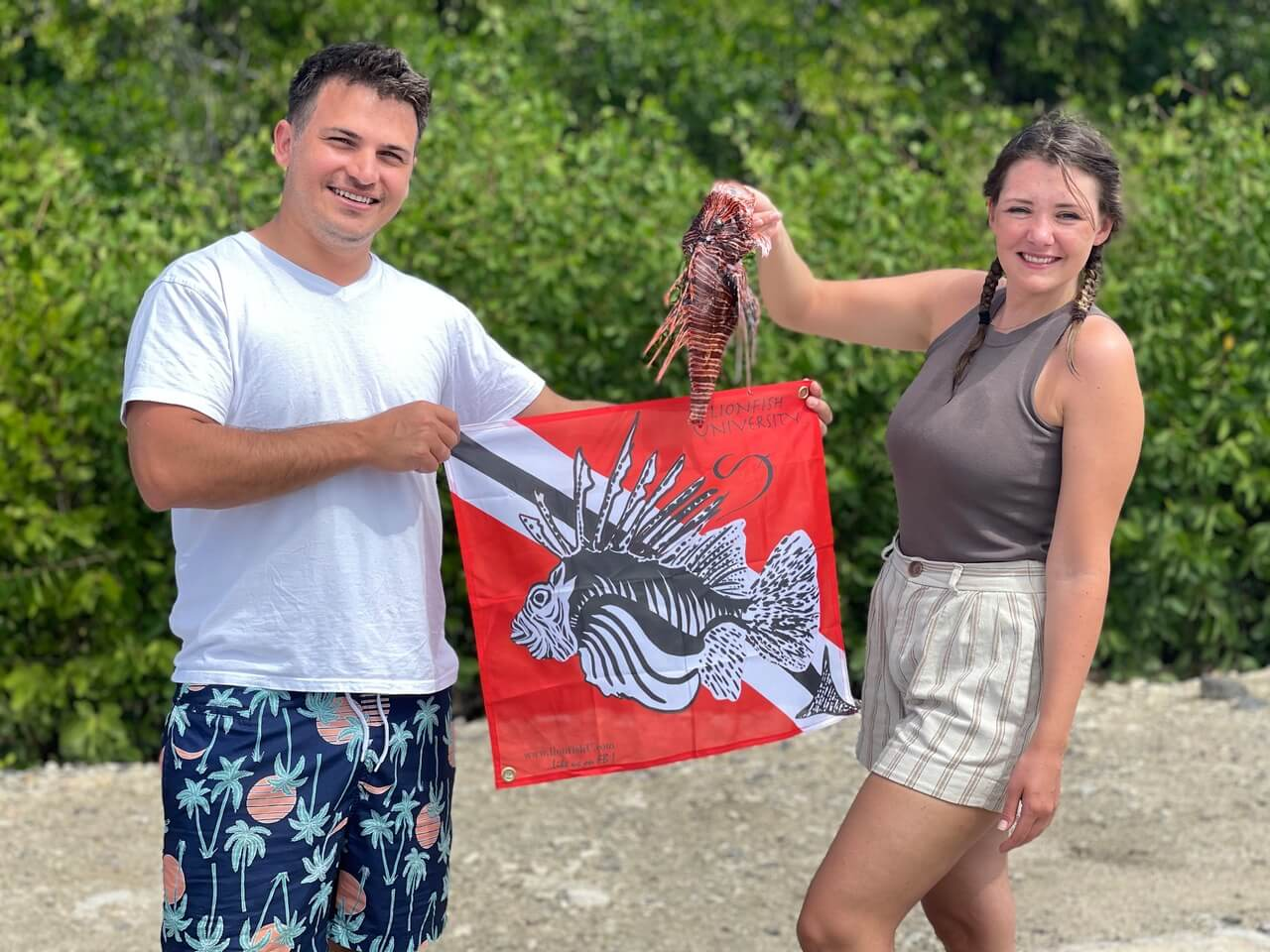 Sabine & Bryan Viera with a scalped Lionfish and the Lionfish University flag.