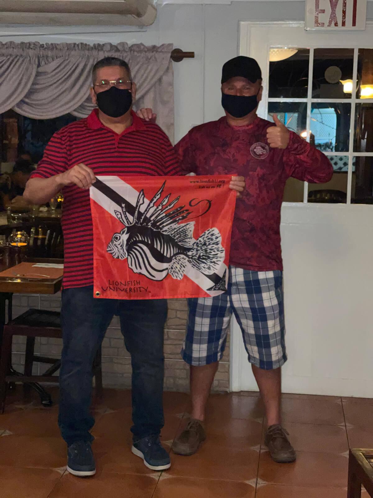 Jose and Roger holding Lionfish University flag