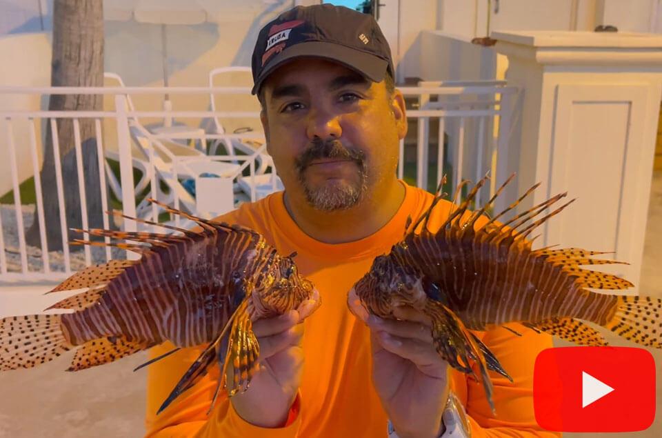 Rafael A. Flores Jr. holding 2 lionfish