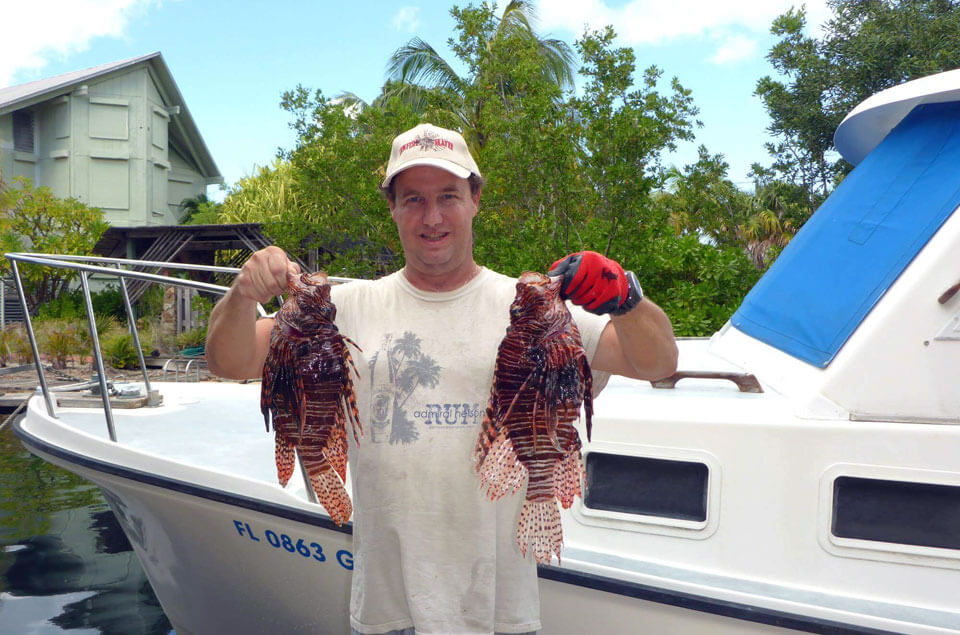 Andy Lowe holding 2 lionfish