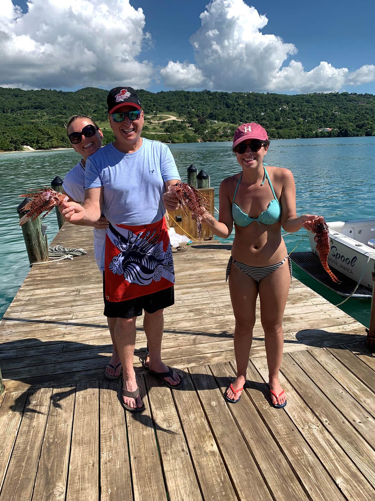 Kelsey M. Muller and Roger J. Muller, Jr holding lionfish