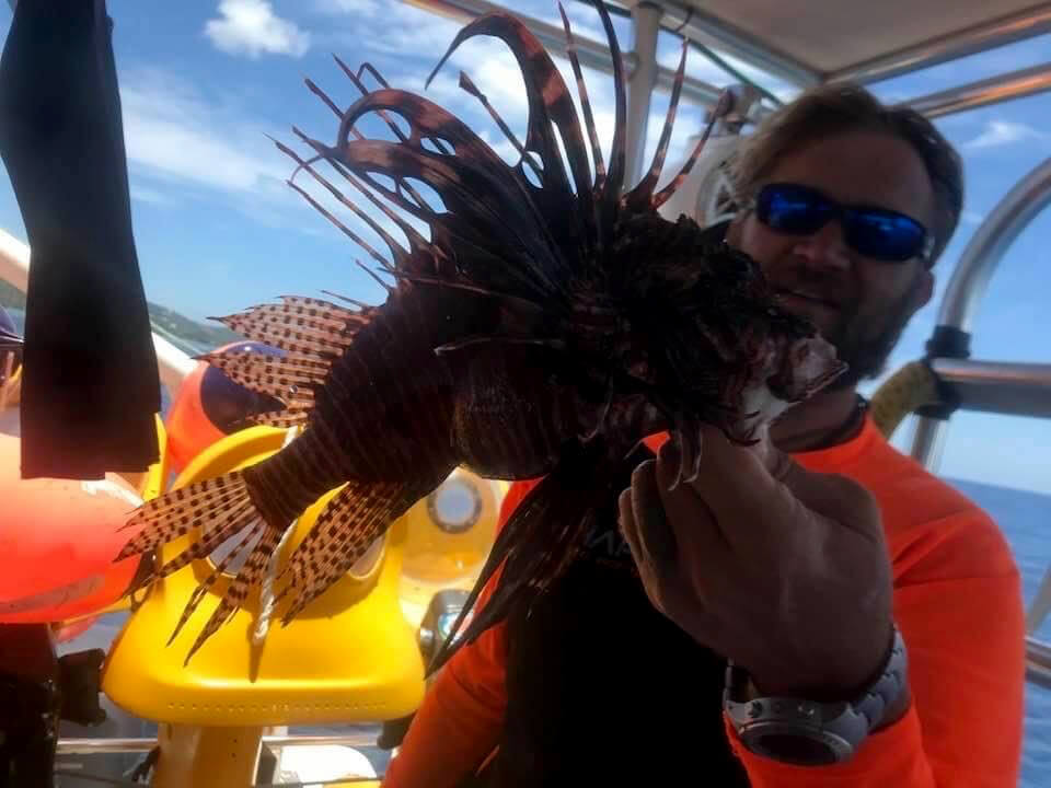 Adam Wise holding a lionfish